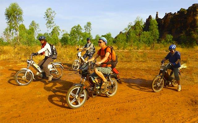 Sur une piste de terre, lors d'un voyage à mobylette au Burkina Faso avec Planet Ride et Guillaume