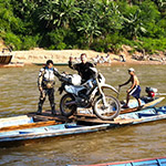 Motard sur une barque lors d'un voyage au Laos à moto