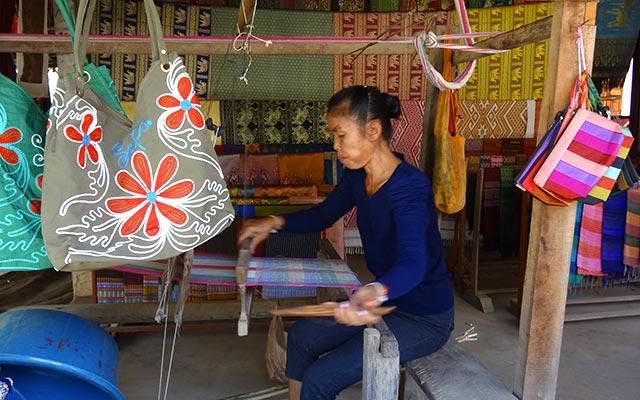 Femme laotienne à l'ouvrage lors d'un voyage au Laos à moto avec Planet Ride