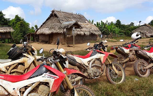 Motos dans un village lors d'un voyage au Laos à moto avec Planet Ride