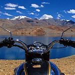 En Royal Enfield au bord d'un lac du Ladakh dans l'Himalaya, lors de votre voyage en Inde à moto avec Planet Ride