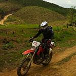 Sur une piste de collines, lors de votre voyage au Laos à moto avec Planet Ride et Charly