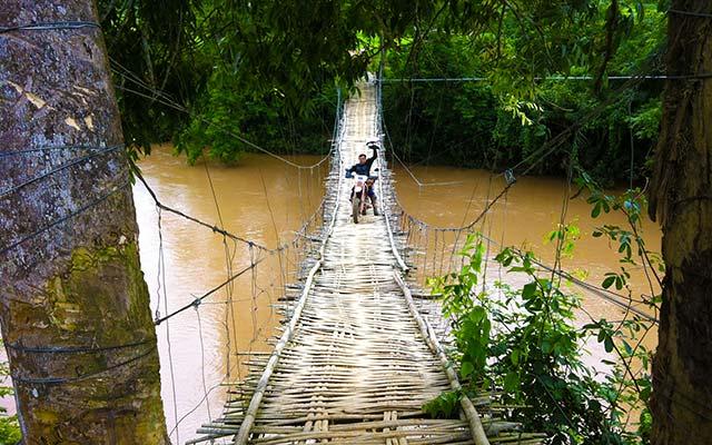 Sur un pont en de bois, lors de votre voyage au Laos à moto avec Planet Ride et Charly