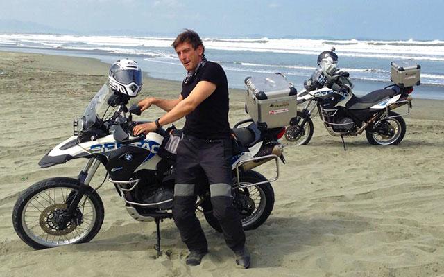 Motard sur la plage, lors de votre voyage aux Philipines à moto avec Planet Ride et Philippe
